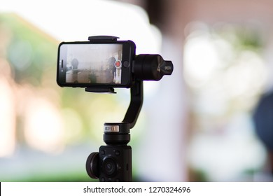 Bang Pa-in, Ayutthaya, Thailand - DEC 21 2018 : Mobile phone iphone 8 is shooting a video using gimbal zhiyun smooth 4 background is bokeh in the morning Video  filming concept