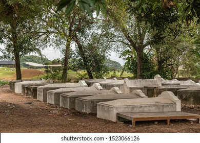 Bang Phra, Thailand - March 16, 2019: Chao Pho Khao Chalak Chinese Cemetery. Group of unused concrete tombs under dark green trees on side of graveyard.