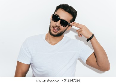 Bang! Playful young Indian man in sunglasses gesturing handgun near head and looking at camera while standing against white background