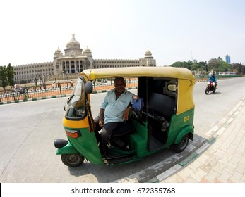 BANGALORE, INDIA - APRIL 12, 2016: a driver of autorickshaw sitting in his car waiting for a passenger