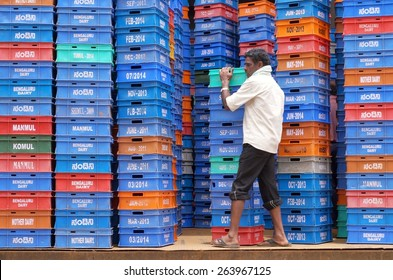 BANGALORE, INDIA - AUGUST 11, 2014: A man carrying colorful milk boxes in a dairy in Bangalore, India.