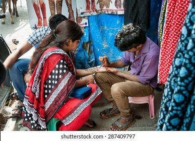 BANGALORE, INDIA - DEC 25, 2014: Unidentified Indian man painting Henna paste on woman's hand at the Russell market  Russell Market is a shopping market in Bangalore, built in 1927 by the British.