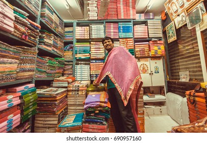 BANGALORE, INDIA - FEB 12: Funny vendor making presentation inside small textile store with dresses and scarfs on February 12, 2017. Capital of the state Karnataka has a population of 8.42 million