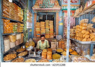BANGALORE, INDIA - FEB 12: Seller of sweets waits for buyers in a colorful shop with biscuits and snacks on February 12, 2017. Capital of the state Karnataka has a population of 8.42 million