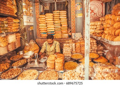 BANGALORE, INDIA - FEB 12: Seller of candy, sweets and cakes sitting in a colorful indian marketplace on February 12, 2017. Capital of the state Karnataka has a population of 8.42 million