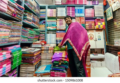 BANGALORE, INDIA - FEB 12: Trader working with female fashion, colorful scarfs and traditional sari in textile store on February 12, 2017. Bangalore is third most populous indian city