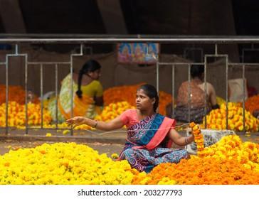 BANGALORE, INDIA - June 06: Woman creating ropes of flowers at KR Market in Bangalore. June 06, 2014 in Bangalore, India.