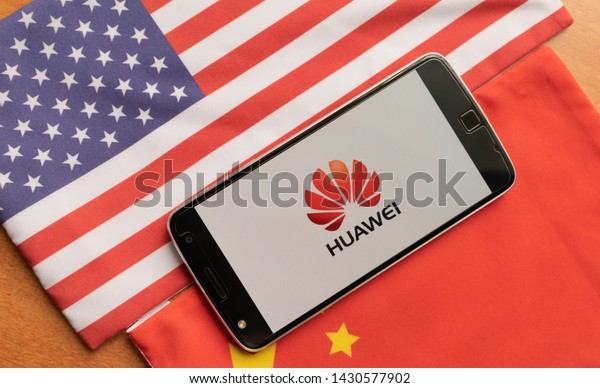 Bangalore, India, June 4, 2019 : Huawei Logo in Mobile, kept on the US and china flag