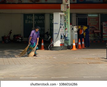 BANGALORE, KARNATAKA, INDIA, APRIL 23, 2018: Clean India, Swachh Bharat. A woman sweeping the floor of a Petrol bunk with two brooms, on a sunny day.