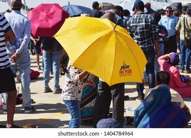 Bangalore, Karnataka, India, February 23, 2019: Yellow and maroon umbrellas give shelter from the intense sun during the AeroIndia air show.