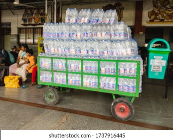 Bangalore, Karnataka, India - January 2020: A large pile of mineral water bottles wrapped in plastic stacked on a trolley at a train station.