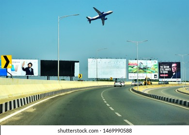 BANGALORE, KARNATAKA, INDIA, MAY 03, 2017: Roads of Bengaluru. Cars on multi-lane airport road and a plane in the blue sky. Hoardings in the background.
