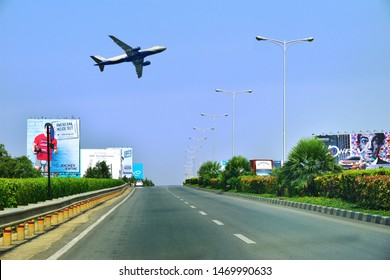 BANGALORE, KARNATAKA, INDIA, MAY 03, 2017:  Road from Kempegowda International Airport, Bengaluru. A plane in the sky and hoardings on either sides of the road.