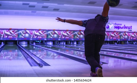 Bangi, Malaysia - April 5, 2019: A adult boy lift up the bowling ball to strike into the tenpins bowling lanes.