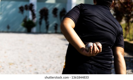 Bangi, Malaysia - April 6, 2019: A boy holding petanque ball or boules in hand behind his back reading to start the game.