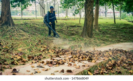 Bangi, Malaysia - August 15, 2019: Park cleaners or workers blowing out the dried leaves on the ground using the high pressure air blower machine to keep the park clean.