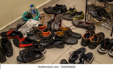 Bangi, Malaysia - November 19, 2019: Variety of men's shoes untidy and disorder in the ground at a men house. Boots, running and casual shoes. Scattered and unarranged a pile of adult shoes.