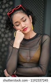 Bangi, Malaysia-28 Sept 2018 : Fashion portraiture of a sexy young asian woman in a shopping mall wearing fishnet style shirt with yellow bra. Fashion lifestyle concept.