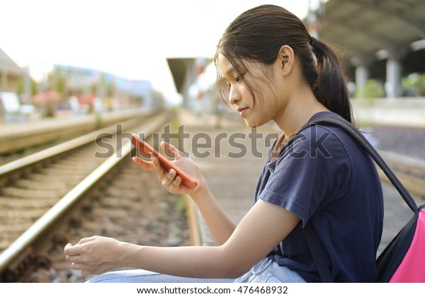 Bangkok ,31 August 2016 : Young Thai girl  playing smart phone at train station ,evening time