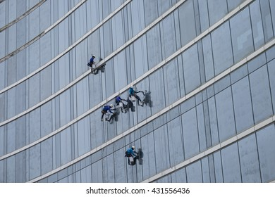BANGKOK - 4 JUNE: Glass cleaner abseiling from a tall building. Window cleaners at work on skyscraper on 4 June 2016 in Bangkok, Thailand.