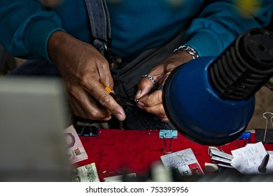 Bangkok - 5 Nov 2017: Detail of a  man's hand producing little handmade beads as fashion accessoiry for Thai teenagers.