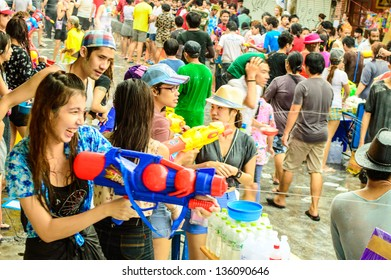 BANGKOK - APRIL 13 :  An unidentified woman with water gun enjoy the Thai traditional new year celebrations (Songkran Day) near Khao San Road on April 13, 2013 in Bangkok, Thailand.