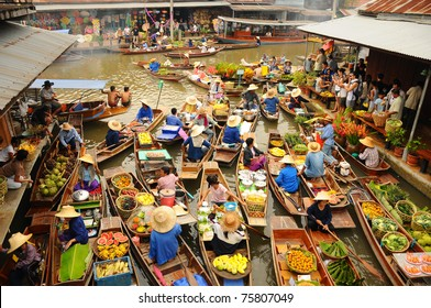 BANGKOK –  APRIL 13: Wooden boats busy ferrying people at Amphawa floating market on April 13, 2011 in Bangkok. A traditional popular method of buying and selling still practiced in Amphawa canals of Thailand.