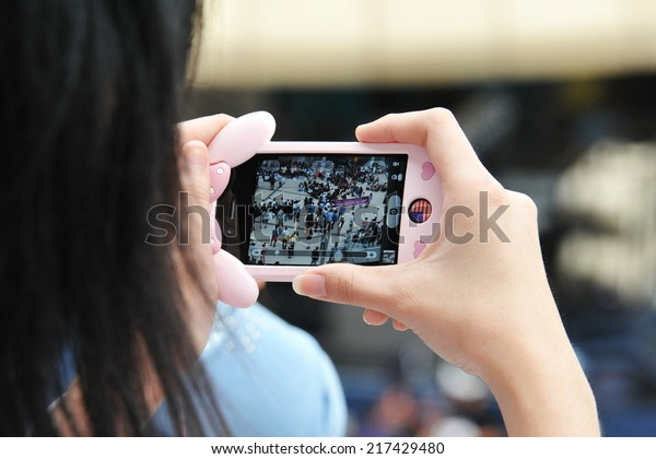 BANGKOK - AUG 17: A protester uses a smartphone to capture an anti-government rally on Aug 17, 2013 in Bangkok, Thailand. Protesters known as V for Thailand protested a controversial amnesty bill.