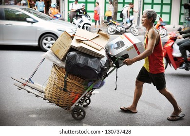BANGKOK - AUG 23: An unidentified man transports discarded materials on Aug 23, 2012 in Bangkok, Thailand. Poverty remains a major problem in Thailand with the average wage under B200 or $4 a day.