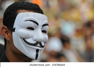 BANGKOK - AUG 4: A masked protester attends a several thousand anti-government rally at Lumpini Park on Aug 4, 2013 in Bangkok. The royalist protesters call for the government to be removed.