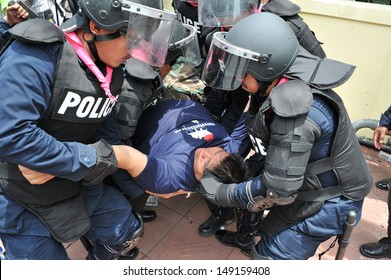 BANGKOK - AUG 7: A protester who collapsed after being arrested is carried by riot police to paramedics during an anti-amnesty rally near parliament on Aug 7, 2013 in Bangkok, Thailand.