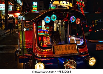 BANGKOK - AUGUST 15, 2016; The colorful neon signs in Bangkok Chinatown are reflected in the windshield of a Tuk Tuk, Thailand's iconic tricycle taxi.