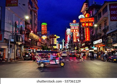 BANGKOK - August 15, 2016: A nighttime scene in Bangkok's chinatown with neon signs. A tuk tuk taxi is crossing the street.