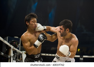 BANGKOK - AUGUST 29: Arican Fikri (R) Thai boxer from Turkey hits his opponent Miyakoshi Soichiro in an international fight competition, on August 29, 2010 in Bangkok, Thailand.