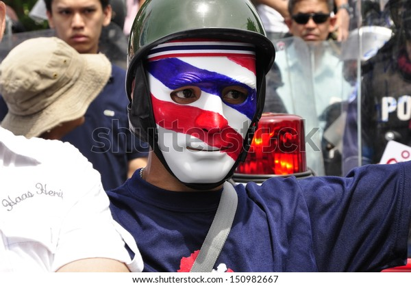 BANGKOK - AUGUST 7, 2013: An anti-government protester wearing a mask painted in the colors of the Thai national flag looks on near Parliament, on August 7, 2013 in Bangkok.