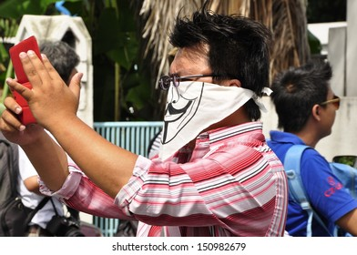 BANGKOK - AUGUST 7, 2013: A man wearing a handmade mask uses his tablet to record the anti-government protesters during a demonstration, on August 7, 2013 in Bangkok.