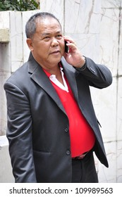 BANGKOK - AUGUST 9: Kwanchai Praipana, Udon Thani based Red Shirt leader talks on a mobile telephone as he leaves the Criminal Court on August 9, 2012 in Bangkok.