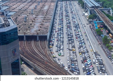 BANGKOK, BTS MOCHIT PARKING LOT, 17 OCT 2018: Top view of many cars and bicycles are parked in the parking lot of BTS Mochit and BTS garage beside road