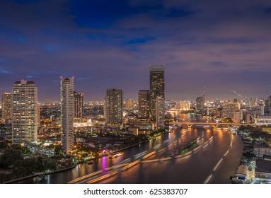Bangkok city by the Chao Phraya river with Sathon bridge at night, Thailand