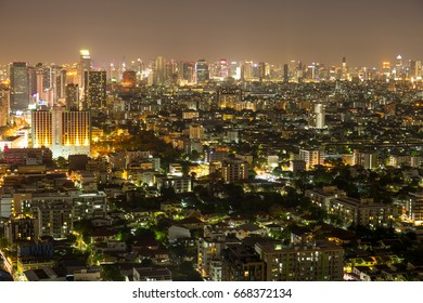 Bangkok city scrapers with high building at night time view from roof top