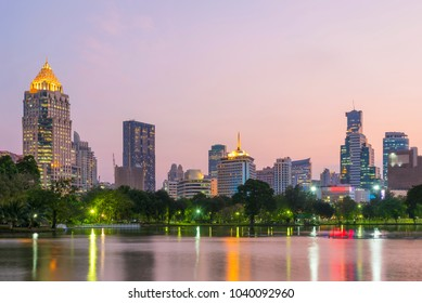 Bangkok cityscape at sunset. Lake and trees in Lumpini park with high building business center around Silom area with sunset sky.