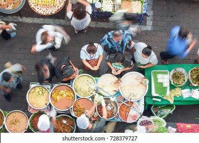 BANGKOK - DEC 16: Unidentified vendors serve food to customers at a streetside restaurant on Dec 16, 2016 in Bangkok, Thailand. Government figures indicate 20,000 registered street vendors in Bangkok.