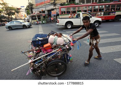 BANGKOK - DEC 18: An unidentified man transports discarded materials on Dec 18, 2013 in Bangkok, Thailand. Poverty remains a major problem in Thailand with the average wage under B200 or $4 a day.