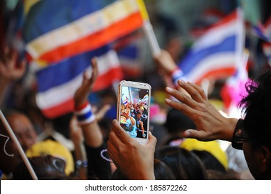 BANGKOK - DEC 20: A passerby uses a smartphone to capture a several thousand strong anti government street rally through the Thai capital's business district on Dec 20, 2013 in Bangkok, Thailand.