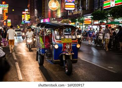 "BANGKOK - DECEMBER 31: Tuk - tuk on Chinatown street at night on DEC 31, 2013 in Bangkok. There are more than 100,000 ""tuk-tuk"" in Bangkok."