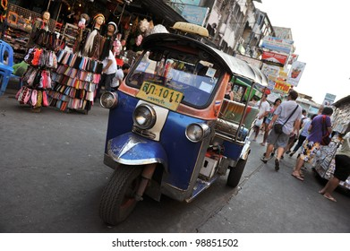 BANGKOK - FEBRUARY 25: A three-wheeled tuk tuk taxi drives along Khao San Road on February 25, 2012 in Bangkok, Thailand. Tuk tuks can be hired from as little as $1 or B30 a fare for shop trips.