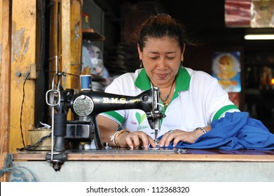 BANGKOK - JAN 11: An unidentified woman operates a sewing machine in a garments factory on Jan 11, 2011 in Bangkok, Thailand. Textile and clothing is Thailand's largest manufacturing industry.