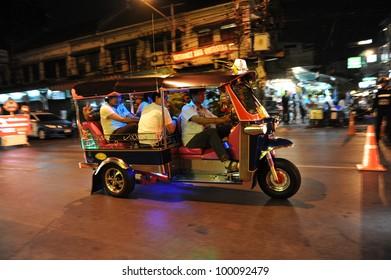 BANGKOK - JAN 15: A three wheeled tuk tuk taxi transports passengers along road on Jan 15, 2012 in Bangkok, Thailand. Tuk tuks can be hired from as little as $1 or B30 a fare for short trips.