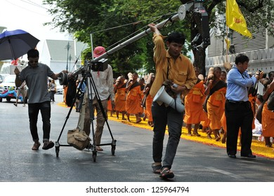 BANGKOK - JAN 25: A film crew use a DSLR mounted on a mobile rig to film monks making a pilgrimage through central Bangkok on Jan 25, 2013 in Bangkok, Thailand.