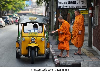 BANGKOK - JAN 26: Buddhist monks hail a tuk tuk taxi on a street in the city centre on Jan 26, 2013 in Bangkok, Thailand. There are an estimated 460,000 ordained monks in the Kingdom of Thailand.